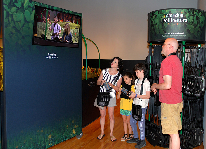 family looking at screen in front of the exhibit