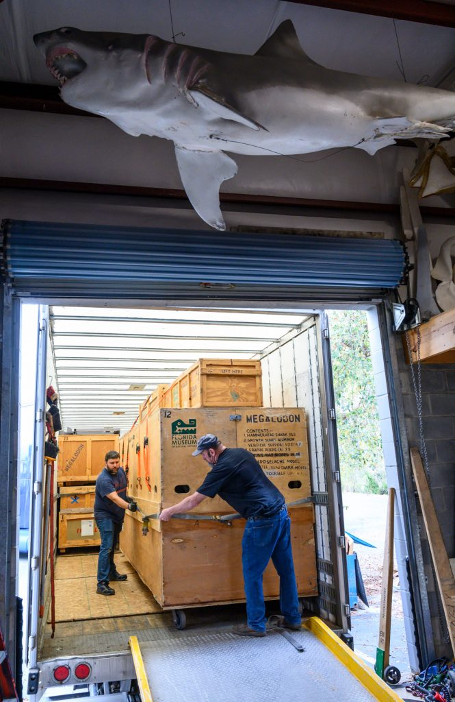 two men securing crates in a truck below a large fabricated shark