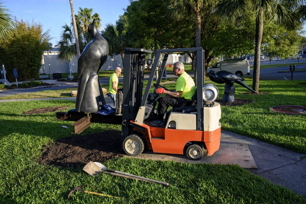 a man in a forklift moving a large statue off the lawn