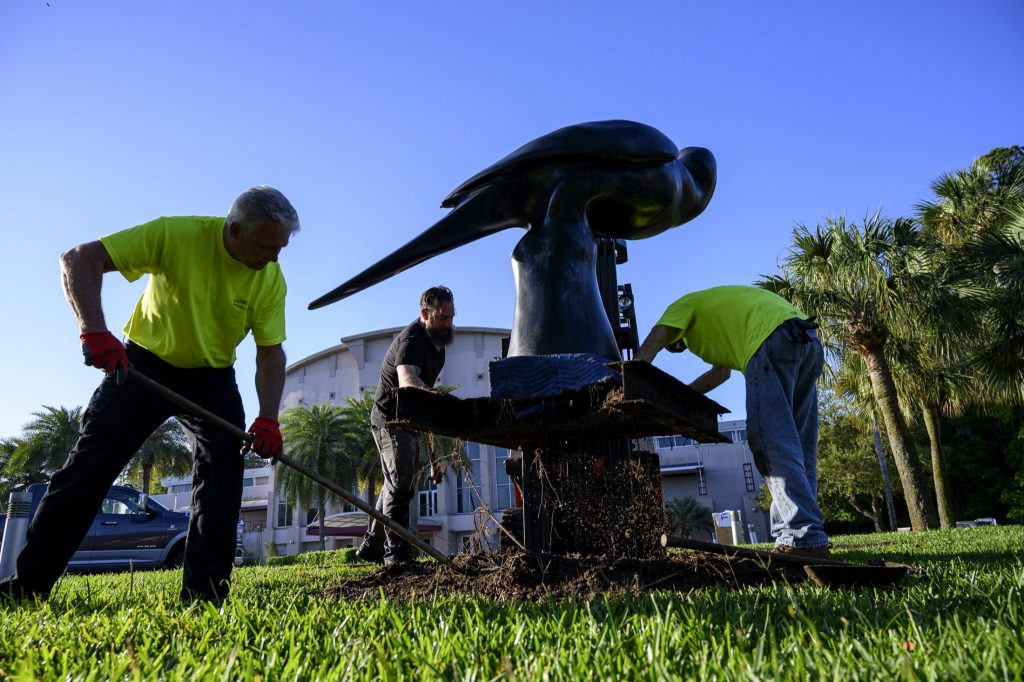 three men dig up the base of a large metal bird statue