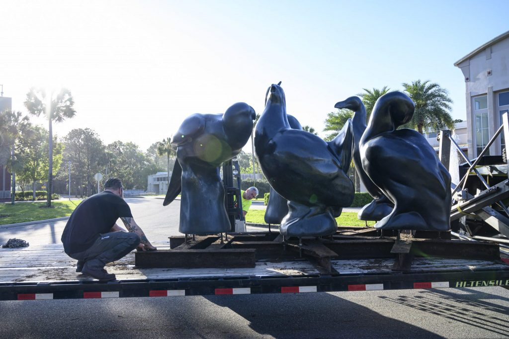 a man secures large bird statues in a flatbed trailer