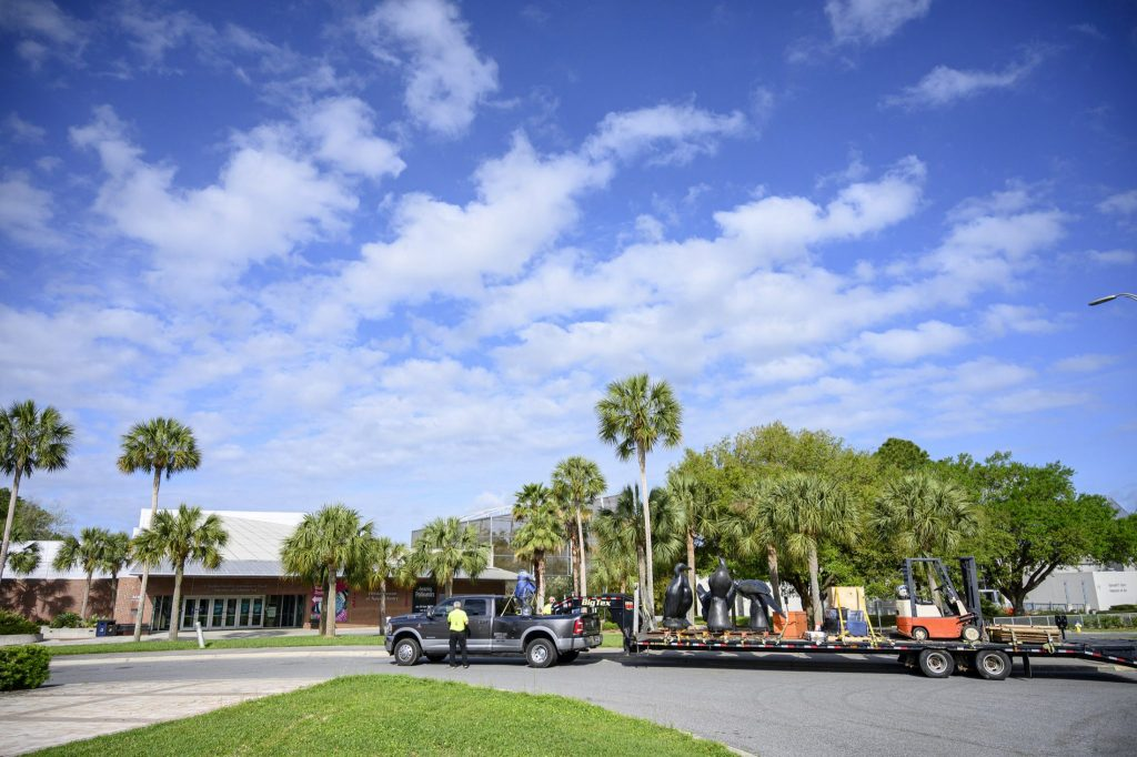 a flatbed trailer and pickup truck in front of the museum under a bright sky and clouds