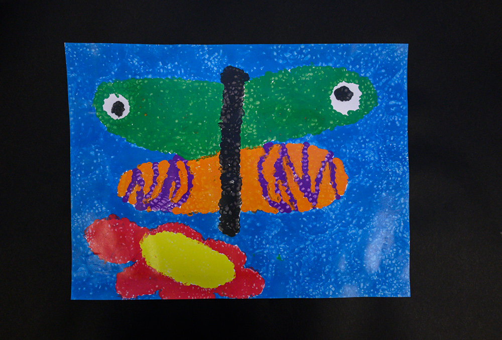 Painting of a green, orange, and purple butterfly.
