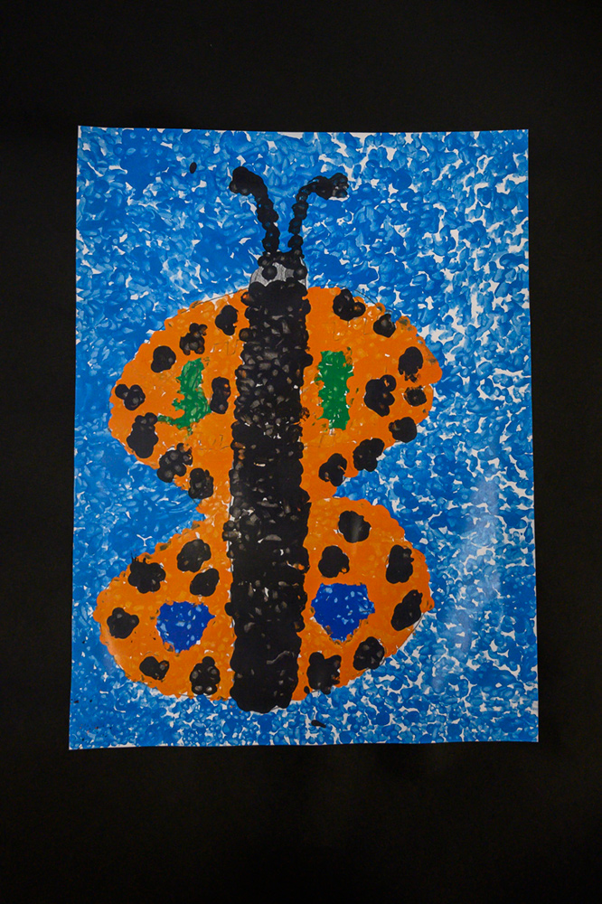 Painting of an orange, black, green, and blue butterfly
