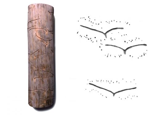 "tree branch covered with ""flying bird"" shaped carving surrounded by small dots"