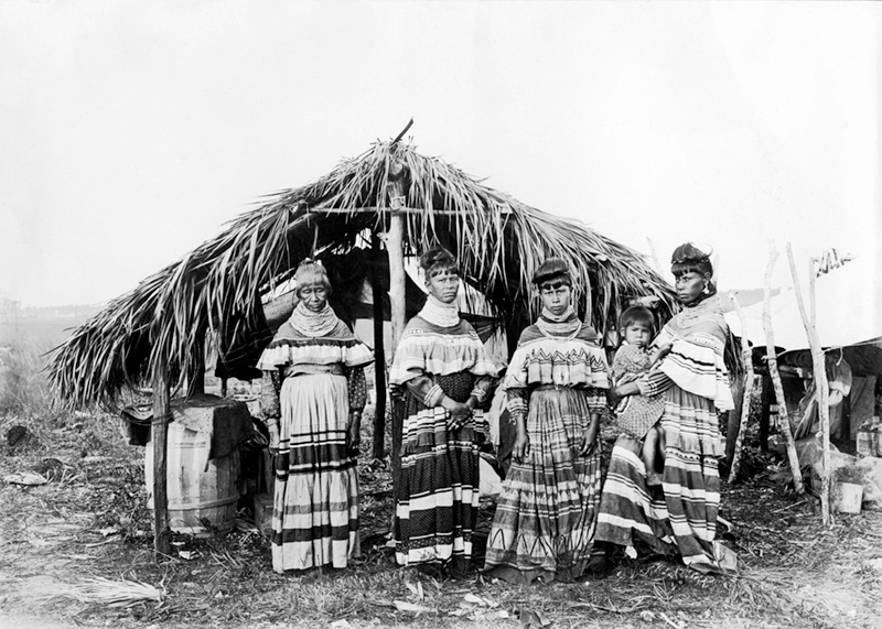 Black and white photo of a Seminole family, four woman, one holding a young child, stand in front their home in the Everglades.