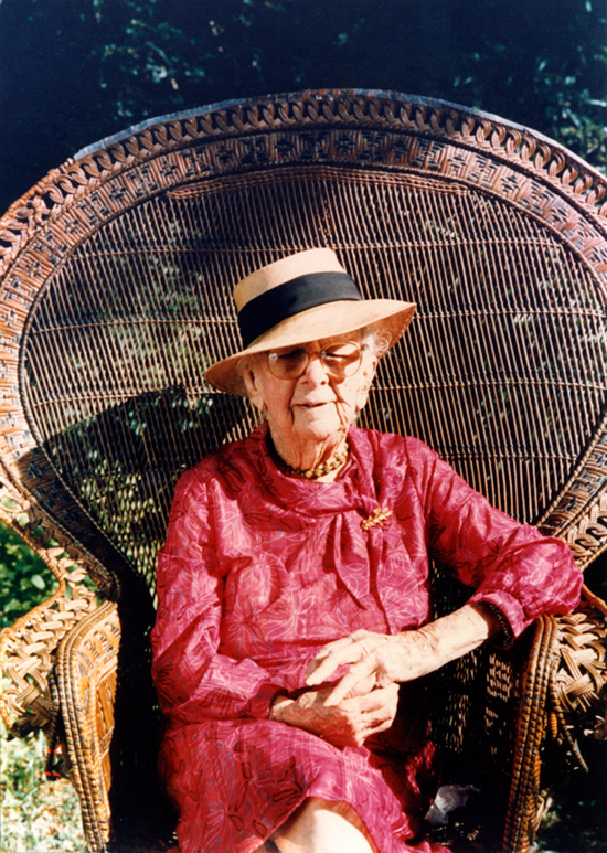 Photo of Douglas in a brightly colored dress and floppy stray hat.