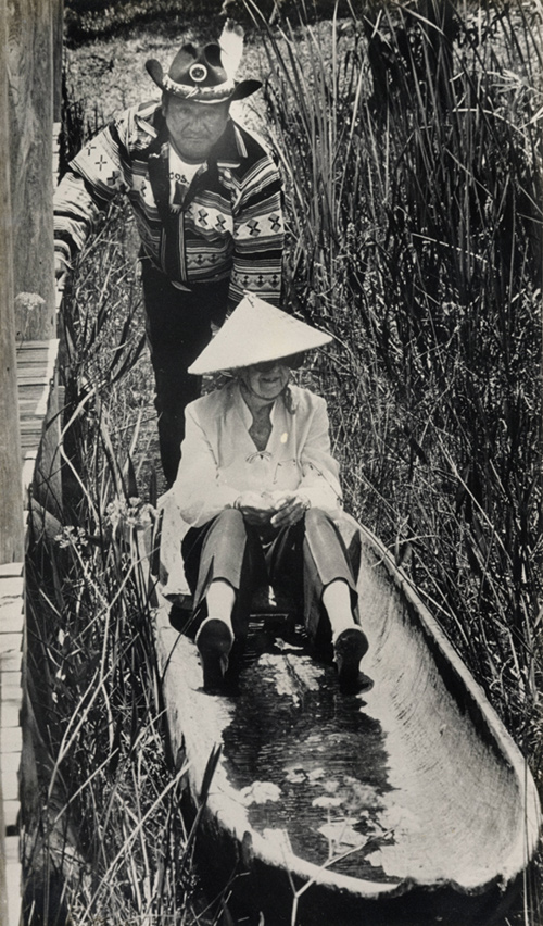 Douglas and George Billie in a canoe surrounded by tall reeds.
