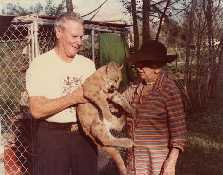 Douglas, wearing her signature straw hat, pets a Florida Panther cub that Frank Weed, manager of the Florida Endangered Species Research Association, is holding.