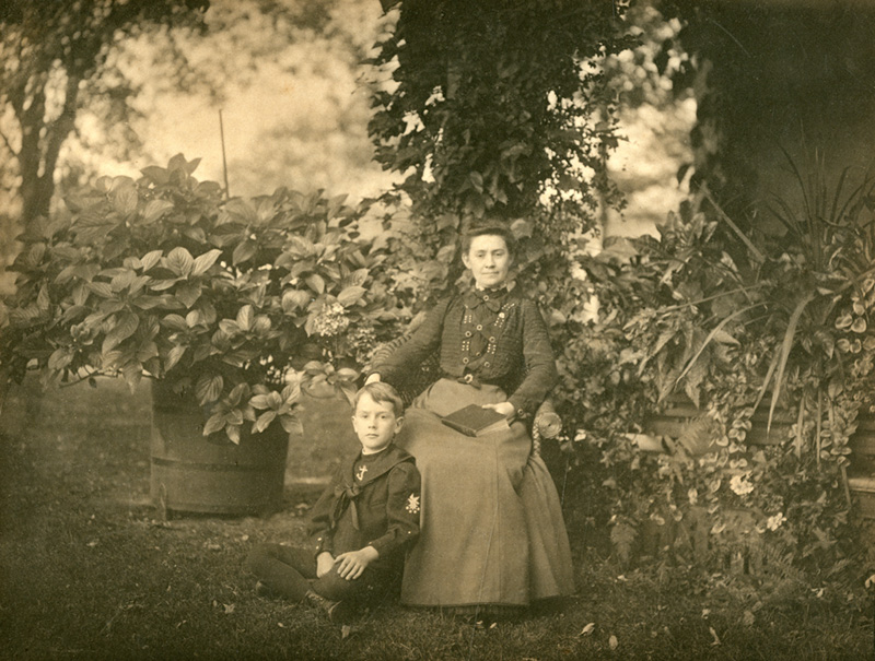 Black and white photo of Jennings with her son sitting in a garden.