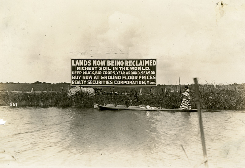 """Seminole woman on a canoe poling past a billboard advertising sale of Everglades land. Billboard reads """"Lands now being reclaimed. Richest soil in the world. Deep much, big crops, year around season buy now at ground floor prices. Realty Securities Corporation, Miami."""""""
