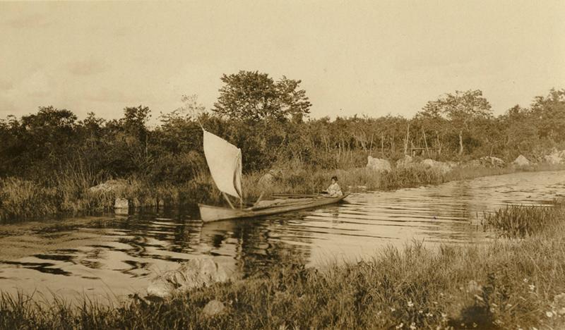 Black and white photo of a boy sailing a canoe.
