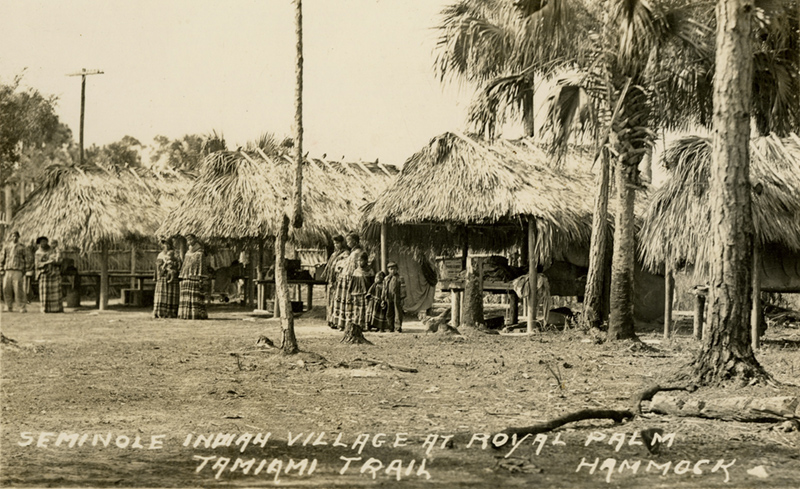 """Seminole Village with grass roofs and woman and children in traditional dress. Handwritten note on the photo reads """"Seminole Indian Village at Royal Palm Hammock Tamiami Trail."""