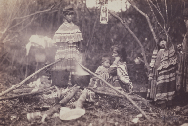 Black and white photo of Seminole woman and children around a camp fire.