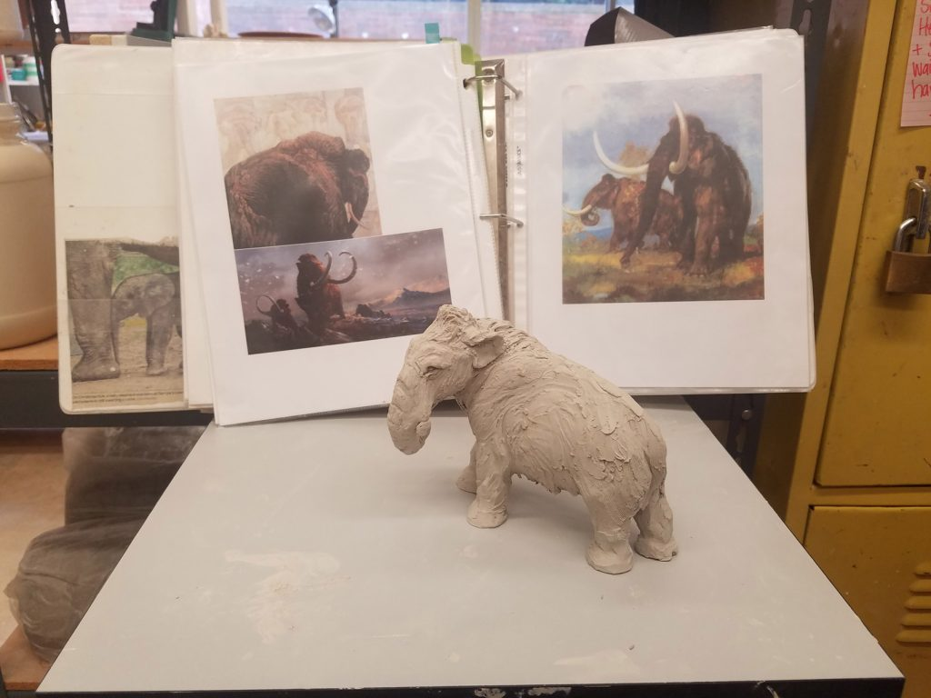 small clay sculpture of a mammoth sits in front of a binder opened to show three images of mammoths.