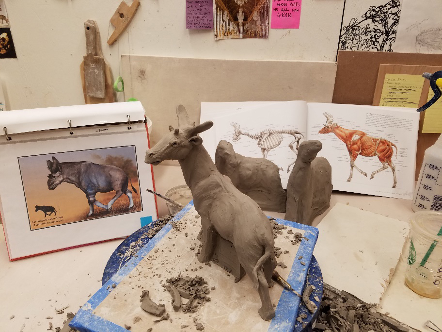 an almost finished clay sculpture sits on wooden board surrounded by clay scraps and sculpting tools. Similar incomplete sculptures and reference books stand behind the sculputre.