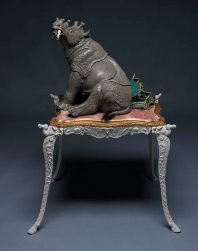 sculpture of a Uintatherium sitting on a broked harpsichord