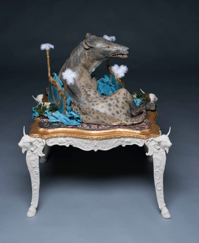 sculpture of an Andrewsarchus sitting on a crushed gold and blue four poster bed