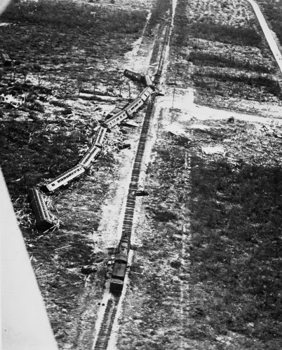 black and white phone of a derailed train. Train cars lay on their side several yards from the train tracks.