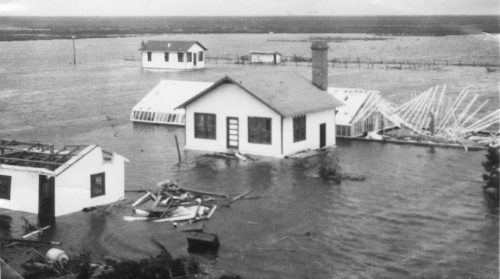 black and white photo of several houses surrounded by several feet of water. One house is missing its roof. Debris can be seen in the water