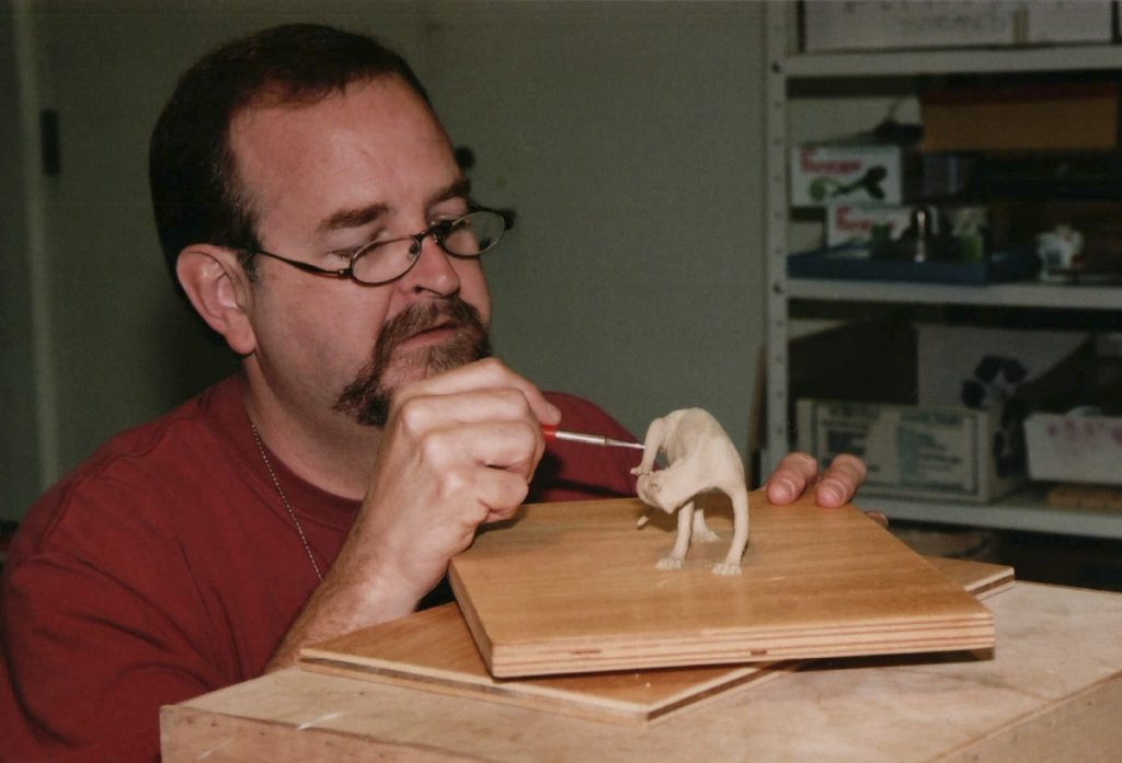 man painting a small model of an animal for the exhibit diorama