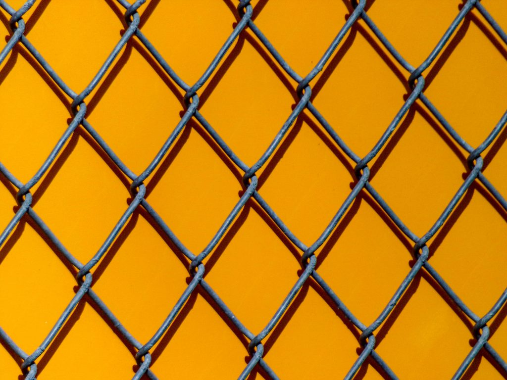 chain link fence in front of a yellow wall