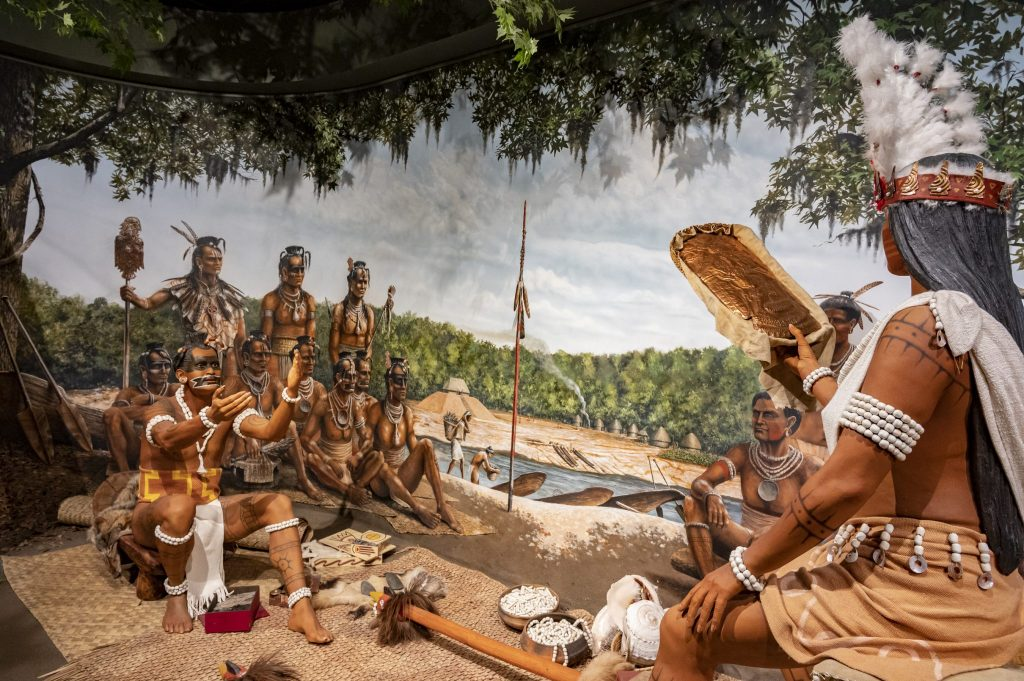 models of native american trading scene in front of painted backdrop