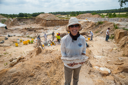 A volunteer holds a plaster jacket with the dig site in the background
