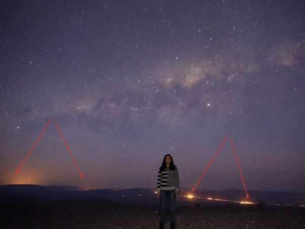 A photo of astrophysicist Rana Ezzeddine standing in front of a sea of stars.
