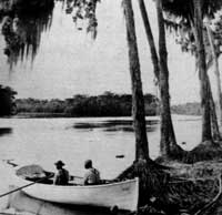 two men sitting in a rowboat on the St. Johns River