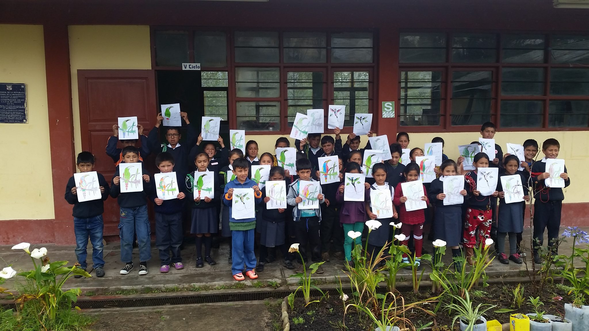 group of children holding bird drawings